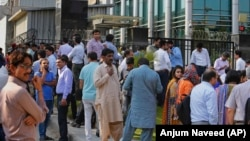 People stand outside an office building after an earthquake is felt in Islamabad, Pakistan, on May 9.