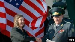 Помощник госсекретаря США Виктория Нуланд передает документы о предоставлении помощи США Виктору Назаренко, первому заместителю главы Госпогранслужбы Украины. Киев, 8 октября 2014 года.