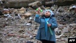 Сирийская девочка среди развалин пускает мыльные пузыри, январь 2017, юг Сирии
