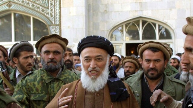 Burhanuddin Rabbani (center) emerges from a mosque surrounded by bodyguards in Kabul last year.