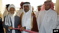 Qatari Assistant Minister for Foreign Affairs Ali bin Fahd al-Hajri (center) and Taliban representative Jan Mohammad Madani (left) at the opening ceremony of the new Taliban political office in Doha, Qatar, on June 18
