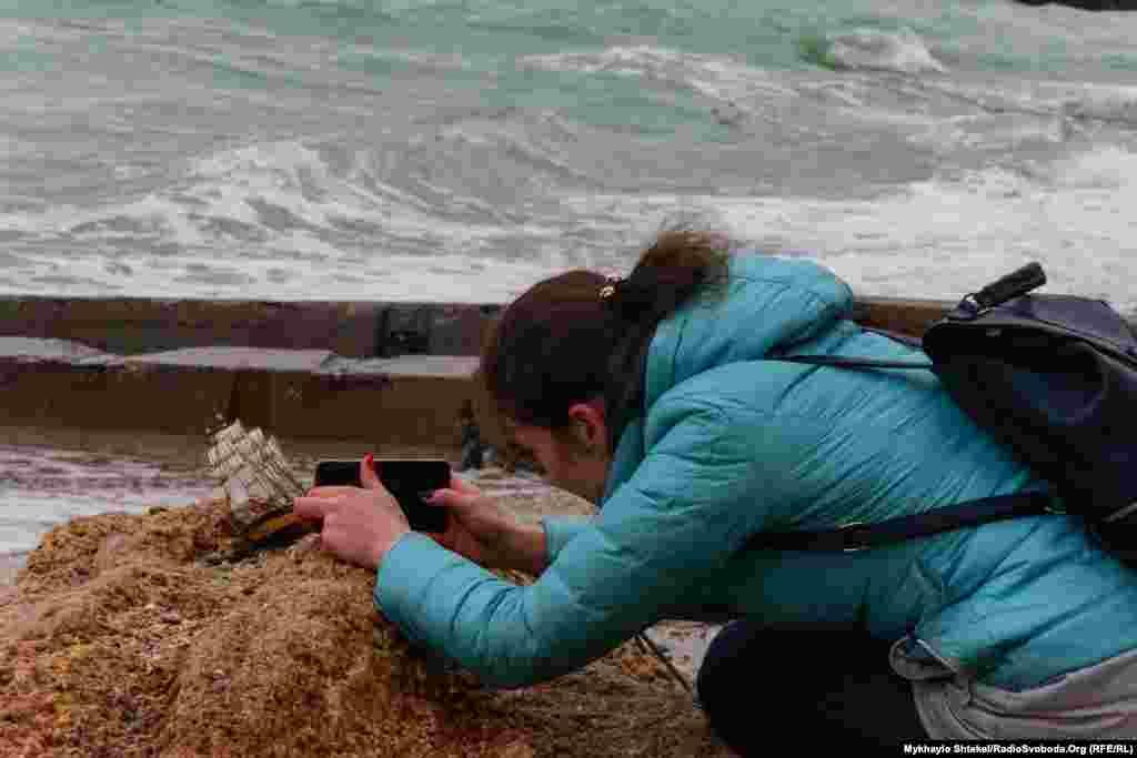 Дівчина принесла на пляж модельку корабля