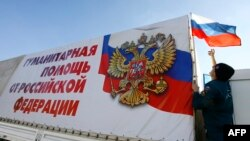 Russia -- A Russian emergency situations ministry driver places a Russian flag on his truck as a humanitarian convoy bound for the regions of Luhansk and Donetsk in Ukraine prepares to depart from the ministry base near Rostov-na-Donu, October 30, 2014