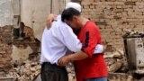 Ош шаарына жакын жердеги айылдардын биринде кыйраган үйүнүн жанында ыйлап жаткандар. 16-июнь, 2010-жыл.