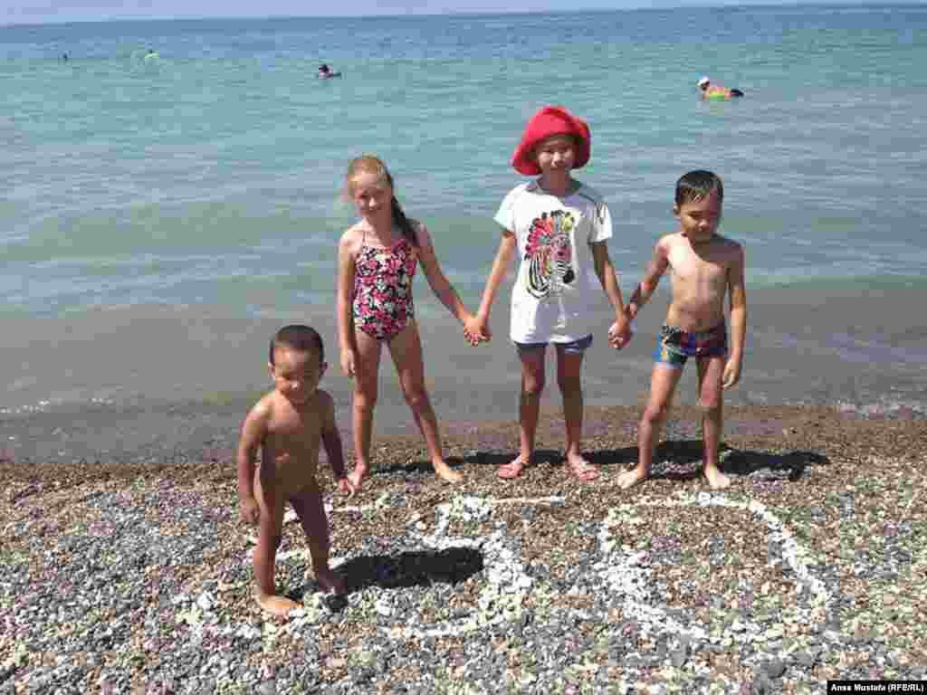 Дети купаются, собирают на берегу камни и выкладывают ими надписи.