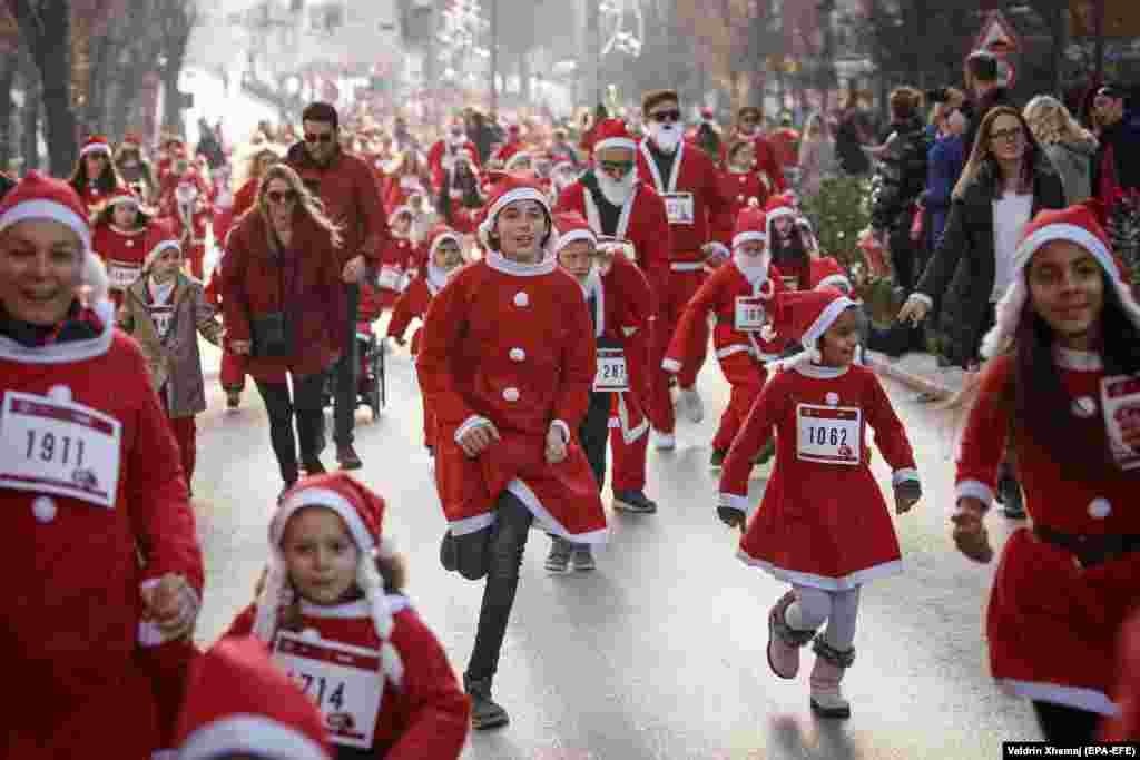 Participants wearing Santa Claus costumes take part in a charity run in Pristina, Kosovo. (epa-EFE/Valdrin Xhemaj)