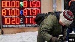 Женщина роется в урне. На заднем плане – курсы валют. Доллар стоит 80 рублей. Москва, 20 января 2016 года.