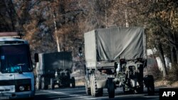 Trucks without license plates tow a 122mm howitzer artillery piece through Makiivka on November 9.