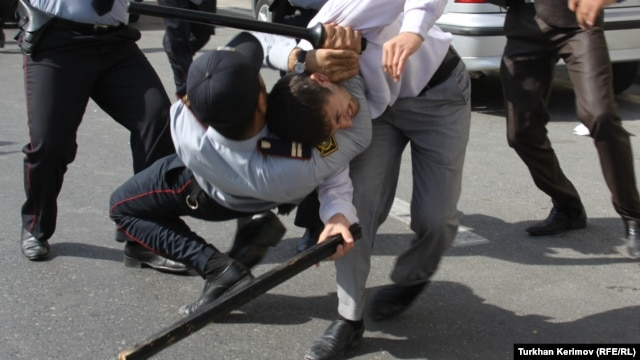 Police and a protester armed with a wooden stick clash in front of the Azerbaijani Education Ministry building in Baku on October 5.
