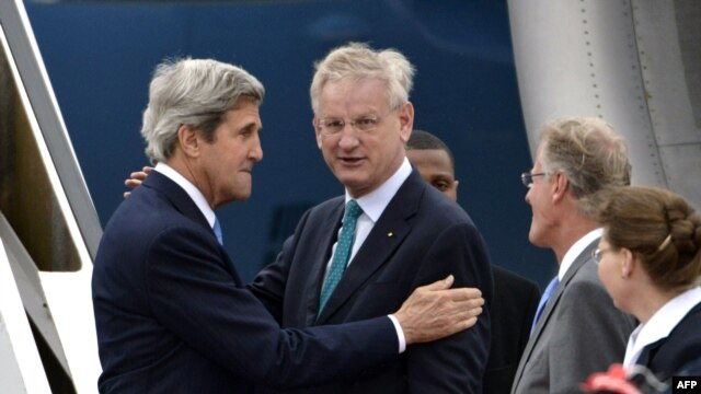 U.S. Secretary of State John Kerry (left) speaks with Swedish Foreign Minister Carl Bildt (center) as he arrives in Stockholm.