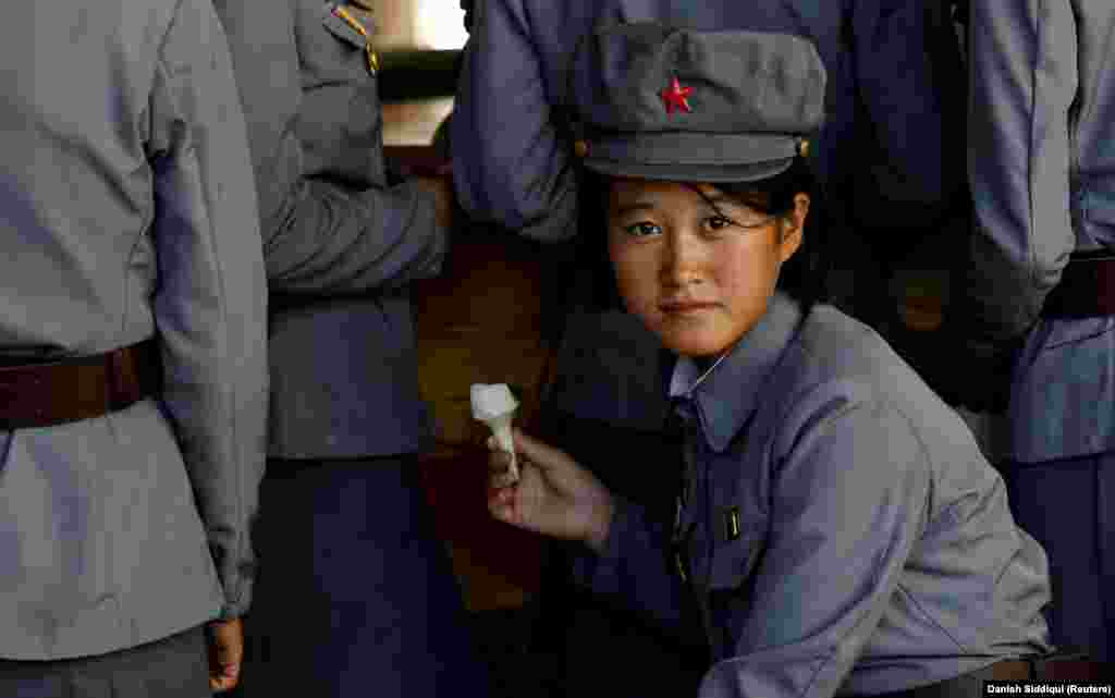 A North Korean soldier eats ice cream as she visits a zoo in Pyongyang. (Reuters/Danish Siddiqui)