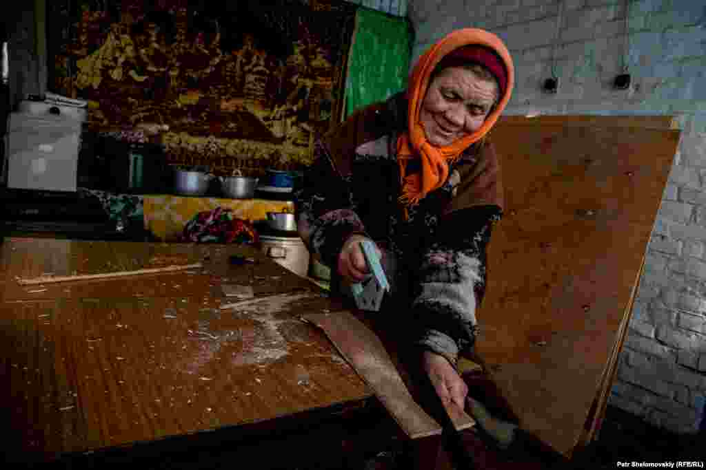 Maria cuts plywood to cover windows shattered by a nearby mortar explosion two days earlier.