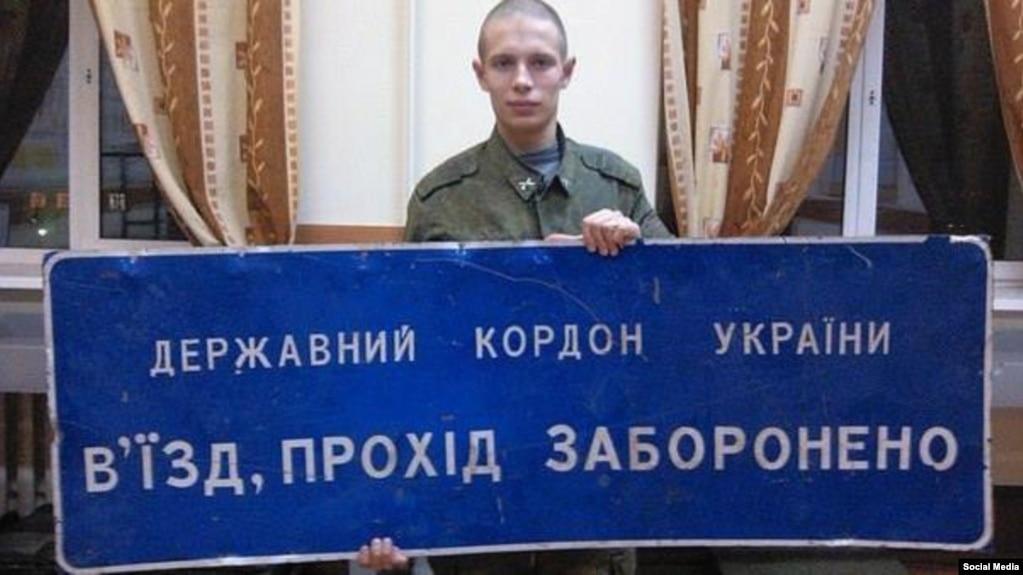 20-річний російський солдат із Саранська Дмитро Шаров позує з табличкою прикордонних військ України, взятою як «трофей»