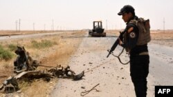 A member of Iraqi government forces inspects a wreckage on the side of a road Qayara Air Base late last month.