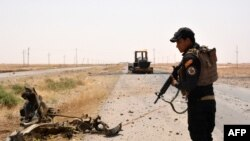A member of Iraqi government forces inspects a wreckage on the side of a road on June 22, 2016 some 40 kilometers west of Qayyarah.
