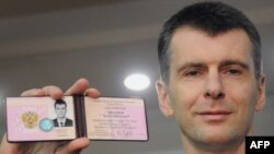 Mikhail Prokhorov shows the document from Russia's Central Election Commission certifying his candidacy for the presidency.