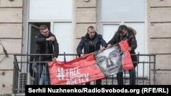 """Станислав Асеев снимает баннер, висевший на балконе редакции издании """"Украинская неделя"""". 2 января этого года"""