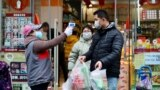 A worker measures body temperature of people leaving a supermarket in Qingshan district following an outbreak of the novel coronavirus in Wuhan, Hubei province, China February 7, 2020. Picture taken February 7, 2020. China Daily via REUTERS ATTENTION EDI