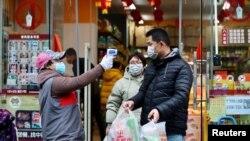 Супермаркетте тұтынушылардың температурасын тексеріп тұрған маман. Қытай, Хубэй провинциясы 7 ақпан 2020 жыл.