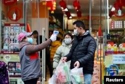Një punëtor shëndetësor kontrollon njerëzit në Vuhan të Kinës.