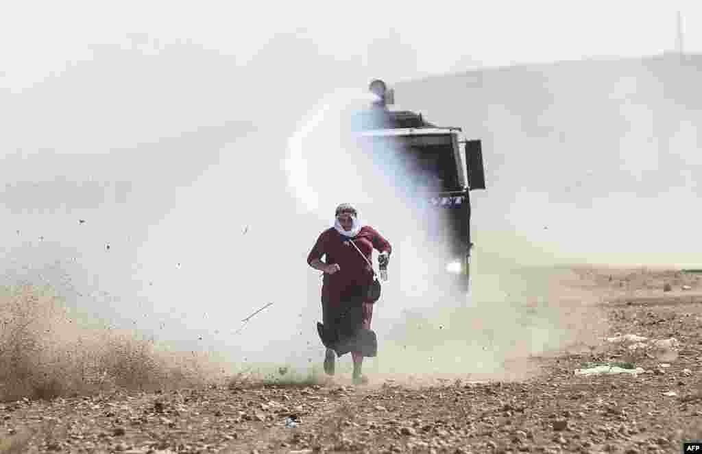 A Kurdish woman runs away from a water cannon near the Syrian border after Turkish authorities temporarily closed the border at the southeastern town of Suruc in Sanliurfa Province. Turkey said on September 22 that some 130,000 people had flooded across its border from Syria as Kurdish fighters battled Islamic State militants trying to capture a strategic town. (AFP/Bulent Kilic)