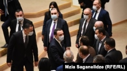 New Prime Minister Irakli Gharibashvili is congratulated by Georgian Dream lawmakers after a confidence vote in his government in a boycotted parliament on February 22.