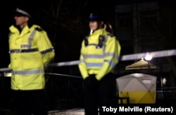 Police officers stand guard beside a cordoned-off area in Salisbury where Sergei Skripal and his daughter were found unconscious on March 4