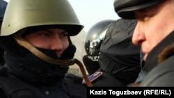 """Лидер оппозиционной незарегистрированной партии """"Алга"""" Владимир Козлов говорит с полицейским на площади Актау. 21 декабря 2011 года."""