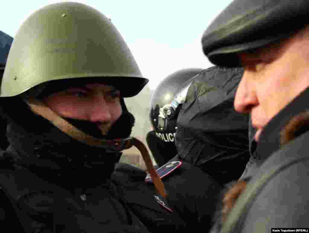 """Тіркелмеген """"Алға"""" партиясының жетекшісі Владимир Козлов орталық алаңда полиция қызметкерімен сөйлесуге тырысып тұр. Ақтау, 21 желтоқсан 2011 жыл"""