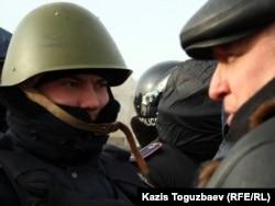 Лидер оппозиционной незарегистрированной партии «Алга» Владимир Козлов разговаривает с полицейским на центральной площади города Актау. 21 декабря 2011 года.