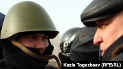 """Лидер оппозиционной партии """"Алга"""" Владимир Козлов говорит с полицейским на площади Актау. 21 декабря 2011 года."""
