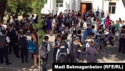 Школьники и их родители во дворе учебного заведения. Иллюстративное фото.