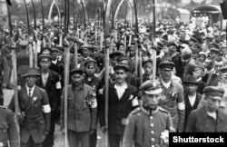 Polish volunteers stand armed with scythes.