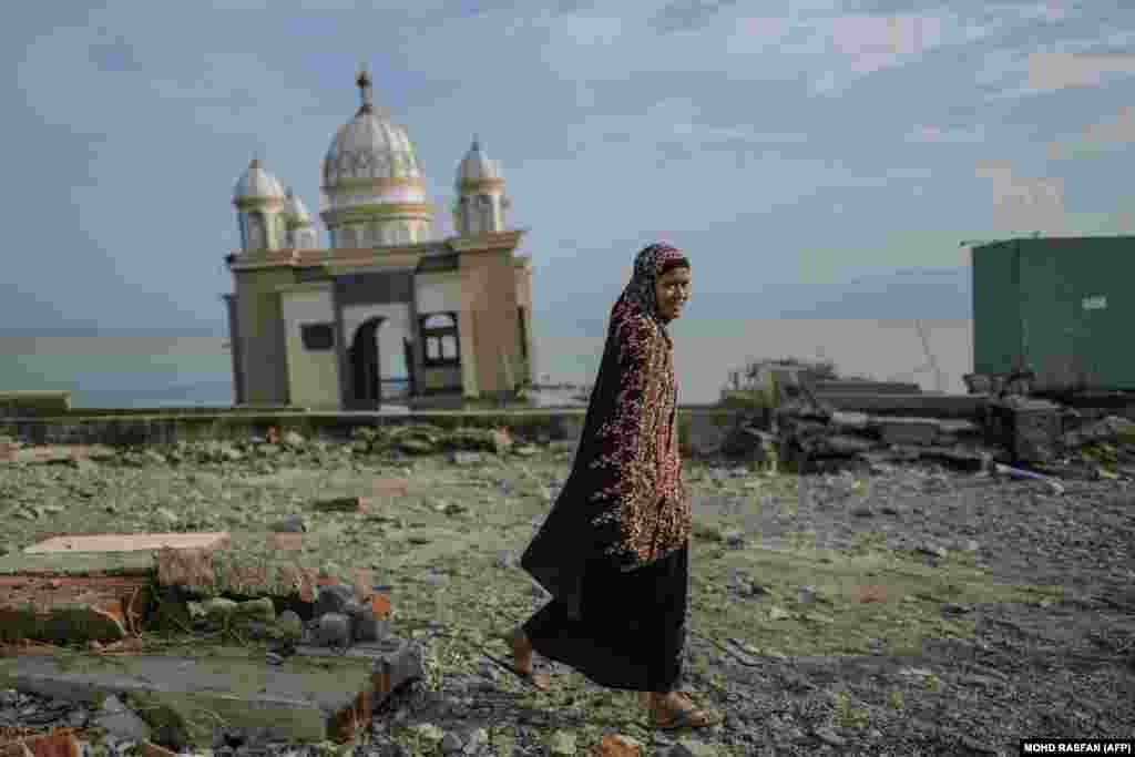 """A resident walks past a damaged mosque on the tsunami-devastated coast of Palu in Indonesia's Central Sulawesi after an earthquake hit the area on September 28. The death toll has passed 1,400, with time running out to rescue survivors and the UN warning of """"vast"""" unmet needs that have fueled looting. (AFP/Mohd Rasfan)"""