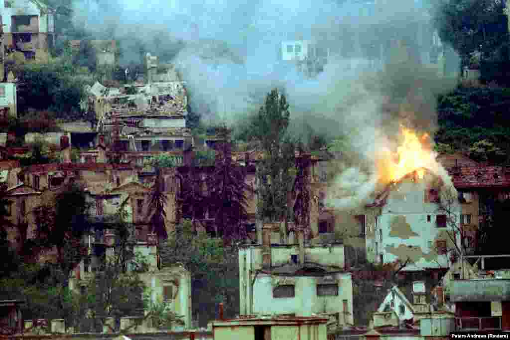 "A house burning in Sarajevo after a direct hit from a mortar in 1994. A UN commission concluded in 1994, with the siege still continuing, that property damage ""includes specifically protected targets such as hospitals and medical complexes, medical facilities...medical personnel, as well as cultural property"" and tens of thousands of apartments."