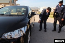 Geo journalist Hamid Mir points to where a bomb was found underneath his car in Islamabad in November 2012.