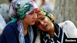 Women mourn as they wait in front of a hospital morgue in the Turkish city of Gaziantep after a suspected bomber targeted a wedding celebration in the city, killing at least 51.