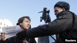 "A policeman detains one of the opposition activists holding the so-called ""single picket"" in support of jailed opposition members in Moscow on January 5."