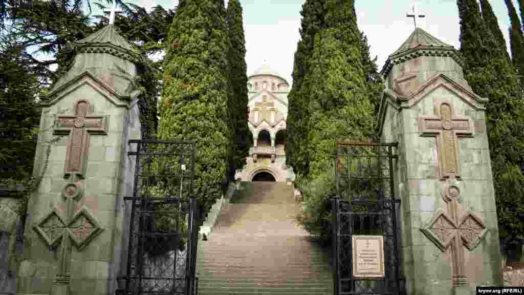 Вхід до церкви обрамляють дві колони з хрестами та масивні ковані ворота. Звідси починаються парадні сходи до кипарисової алеї, що веде до храму
