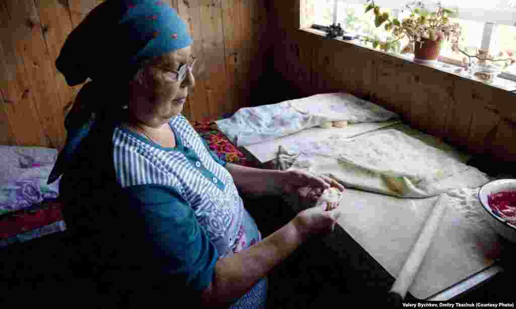 A woman prepares a traditional dish, blueberry dumplings.