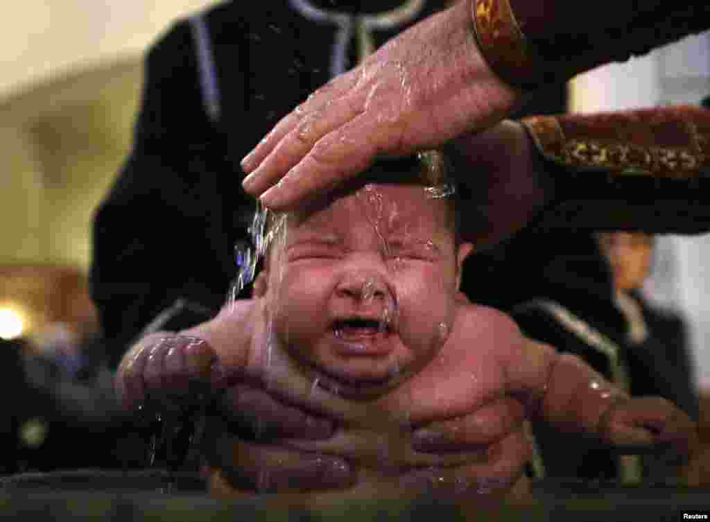 A baby is baptised during a mass baptism ceremony on the Orthodox feast of Epiphany in Tbilisi, Georgia, on January 19. (Reuters/​David Mdzinarishvili)