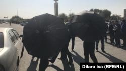 Неизвестные с зонтами мешают вести съемку корреспонденту Азаттыка. Шымкент, 26 октября 2019 года.