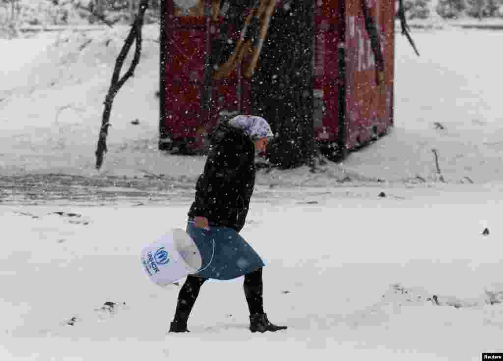 A Syrian woman braves a snowstorm at a refugee camp north of Athens, Greece, on January 10. (Reuters/Yannis Behrakis)