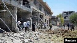 رجال يتفحصون موقعاً في دوما قال ناشطون ان قوات موالية لبشار الأسد ضربته.