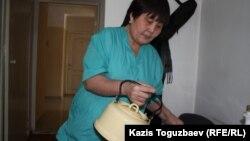 """Сотрудница Дома ветеранов наливает чай в комнате """"афганца"""" Бауыржана Джасымбекова. Алматы, 18 февраля 2014 года."""
