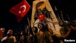 Таксим алаңыда тұрған әскерилер мен Түркия туын ұстаған адамдар. Стамбул, 16 шілде 2016 жыл.