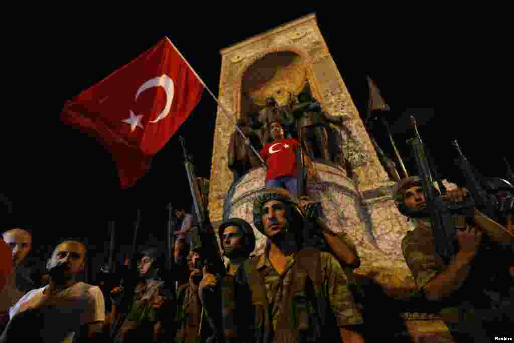 Members of the Turkish military are posted on Taksim Square in Istanbul as civilians wave Turkish flags.