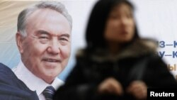 Kazakhstan -- A woman walks past an election poster of Kazakh President Nursultan Nazarbaev in Almaty, 22Feb2011