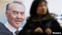A woman walks past an election poster of Kazakh President Nursultan Nazarbaev in Almaty on February 22.