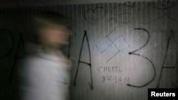 "A woman walks past a swastika and the inscription ""Death to Jews' painted on a wall in an underpass in Kyiv. File photo"